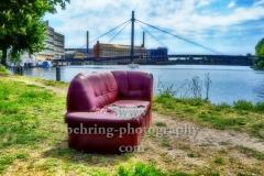 """kaputtes rotes Sofa auf einer Wiese mit Blick auf die Spree, Kaisersteg und den HTW Campus Wilheminenhof, """"STADTANSICHTEN"""", Berlin, 10.05.2020"""